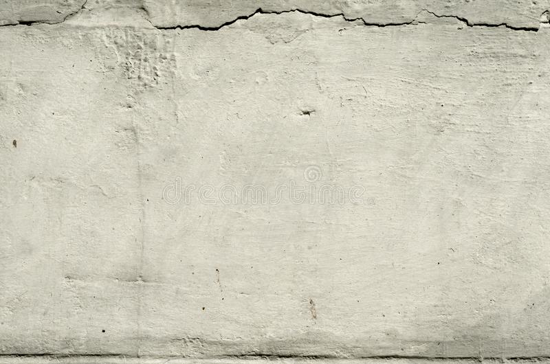 Texture old concrete wall with remains of plaster with cracks. White texture old concrete wall with remains of plaster with cracks royalty free stock images