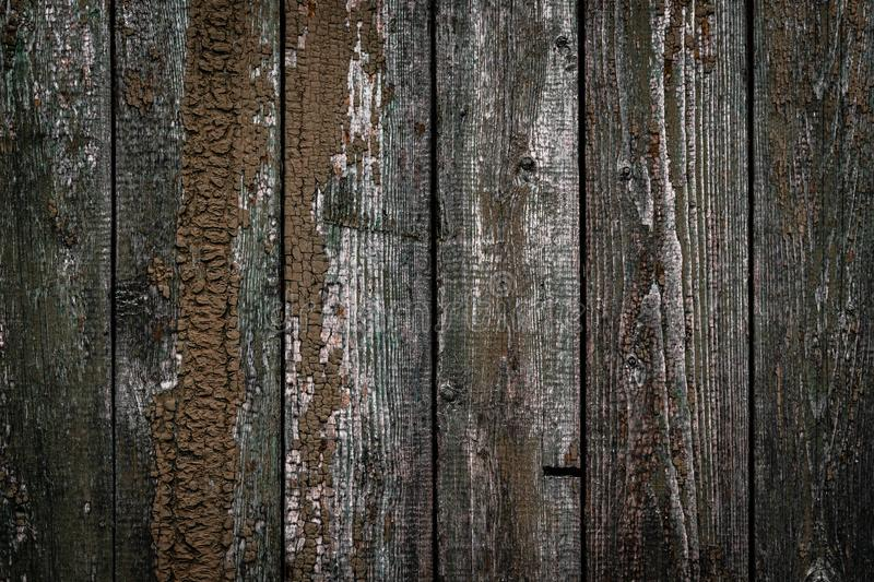 The texture of the old wooden fence with peeling paint and cracks. Wallpaper for vintage design royalty free stock image