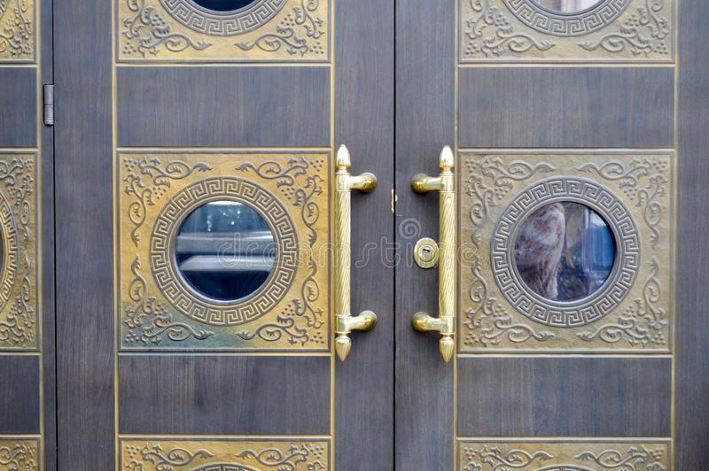 Texture of old decorative beautiful wooden door gates with patterned ornaments elements and gold door handles. The background royalty free stock photo