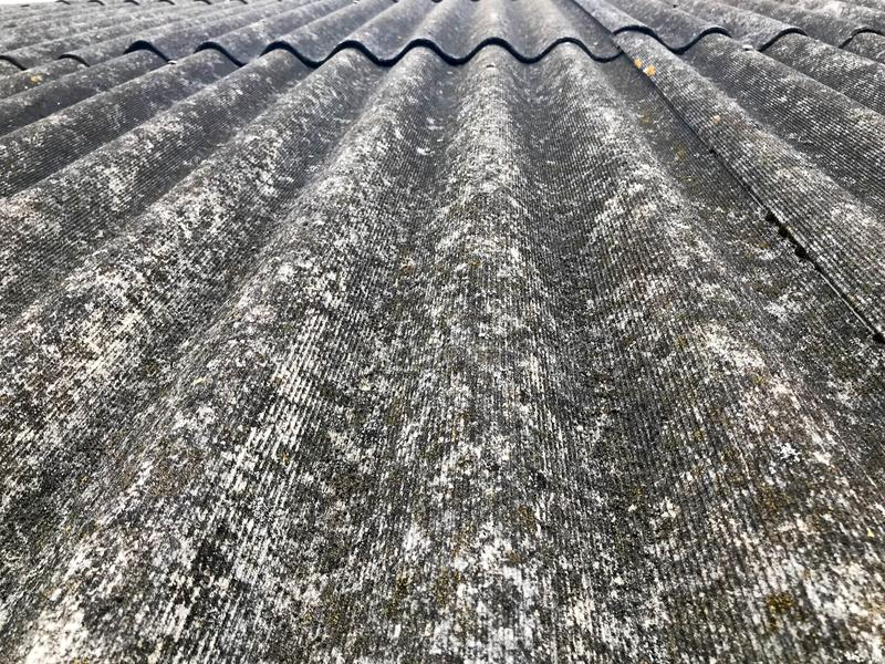 Texture of old dilapidated bulk gray slate, sloping roof of asbestos located vertically covered with green moss royalty free stock photos