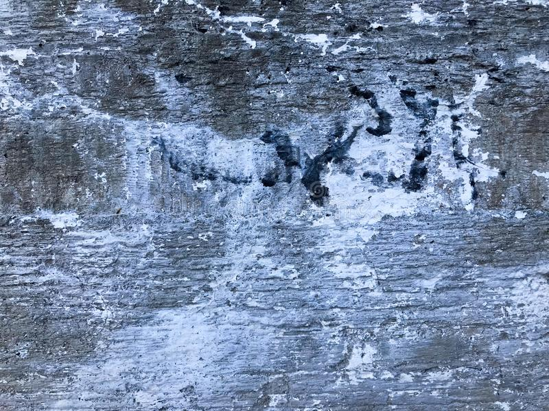 Texture of the old gray concrete cement plaster wall with cracks dent holes patterns and divorces, breakaway pieces, background. stock photography