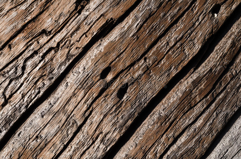 The texture is an old gray, rotted wooden board with deep wavy cracks and holes. stock photo