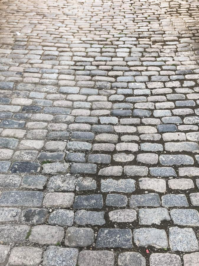 The texture of the old pedestrian stone-paved stone brick gray road with seams. The background stock photo