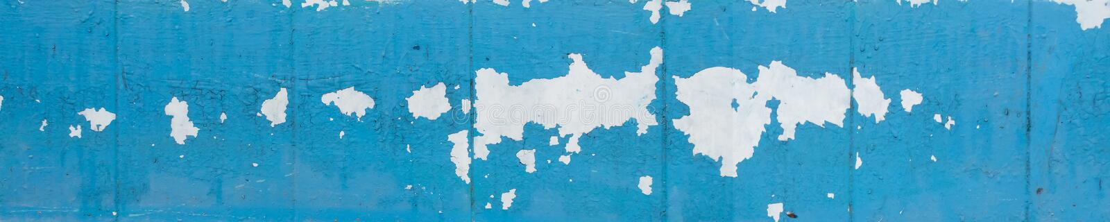 Wall with old peeling blue paint. Texture of old peeling paint, vintage graffiti background, it`s time to make repairs, cracked paint texture.  Clipart stock photo