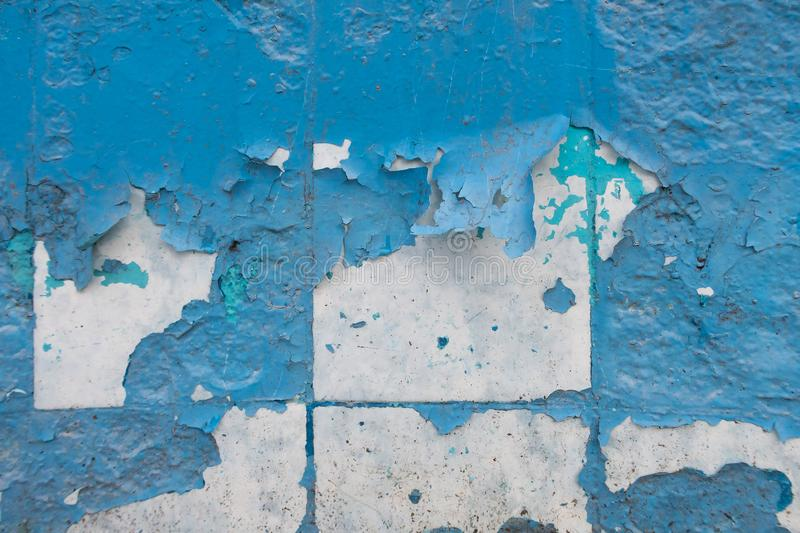 Wall with old peeling blue paint. Texture of old peeling paint, vintage graffiti background, it`s time to make repairs, cracked paint texture.  Clipart royalty free stock image
