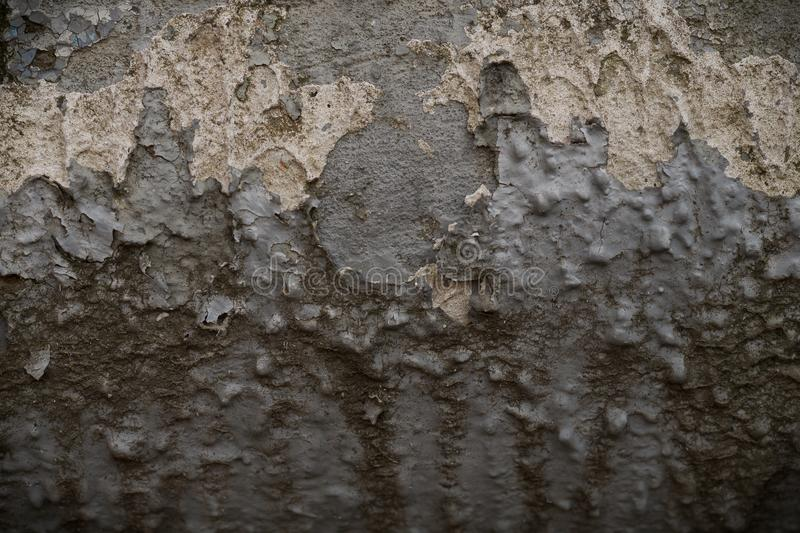 Grunge background collapsing convex surface of the old wall in blue-gray color. Texture of old plaster and paint. Several layers of coating are separated and stock photography