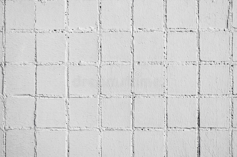 Texture and old square tiles of beige white color tile wall.  royalty free stock photography