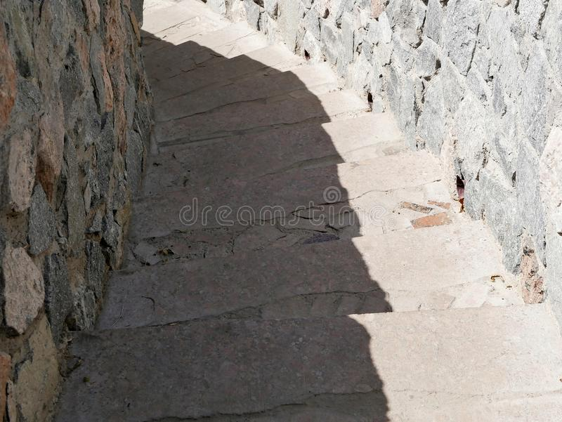 The texture of the old stone staircase with a spiral descending downwards stock photos