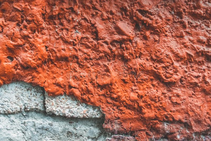 Texture of old broken red wall. Background of Wall fragment with broken stucco and bricks. Texture of old wall. Background of Wall fragment with broken stucco stock images