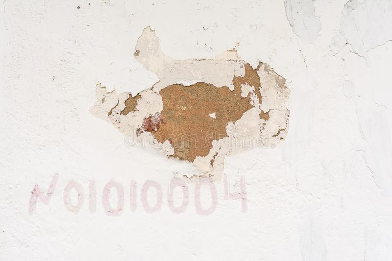 Texture of an old wall with ruined stain stucco, white surface of the exterior painted wall, abstract background royalty free stock photo