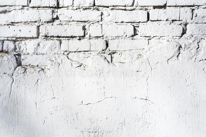 Texture of old white brick wall with destroyed plaster layer and shadows from trees, architecture abstract background stock images
