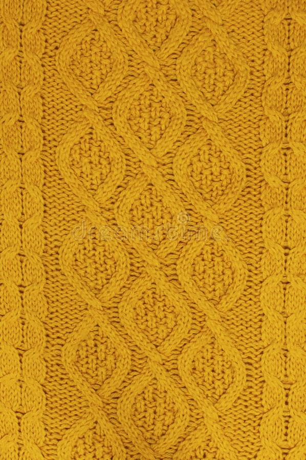 The texture of an orange autumn sweater. Knitted background. Knitted texture. A sample of knitting from wool. royalty free stock images