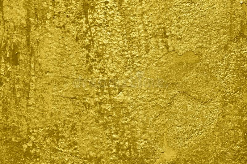 Texture of the plastered wall airbrushed with golden graffiti paint. Plastered wall sprayed with graffiti paint of golden color. Glossy bright grunge background stock images