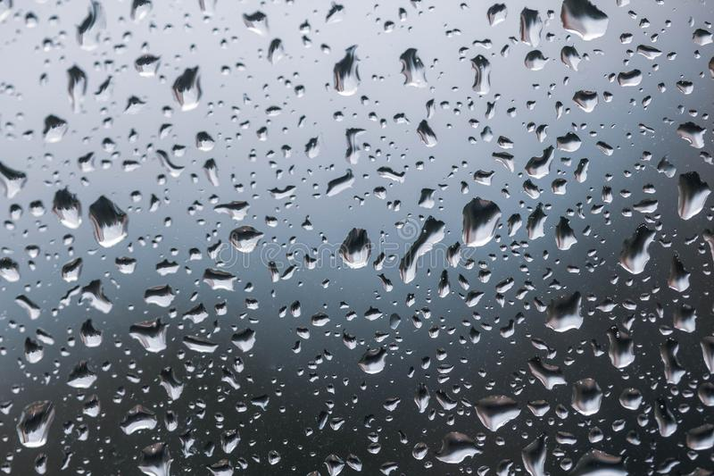 The texture of rain drops on the glass close-up. Macro transparent water drops on blue background royalty free stock images