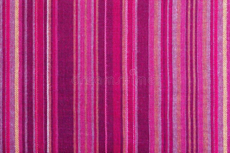 Texture rayée de tissu avec des couleurs chaudes multiples pourpres, pourpre, magenta, rose, rouge, marron, orange, jaune photographie stock libre de droits