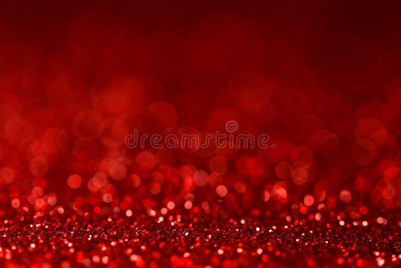Texture rouge de scintillement de plan rapproché avec la lumière de bokeh de tache floue images stock