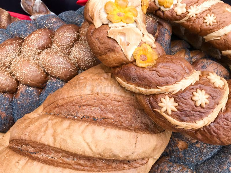 Texture of ruddy brown wheat lush tasty white loaves, bread, black poppy buns. The background.  stock photography