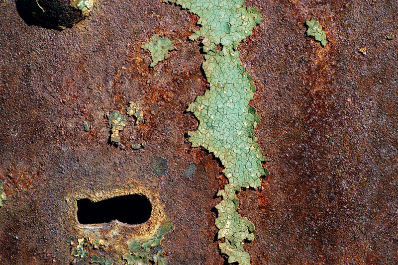 Texture of rusty iron, cracked green paint on an old metallic surface, metal surface with a bolt and a keyhole royalty free stock image
