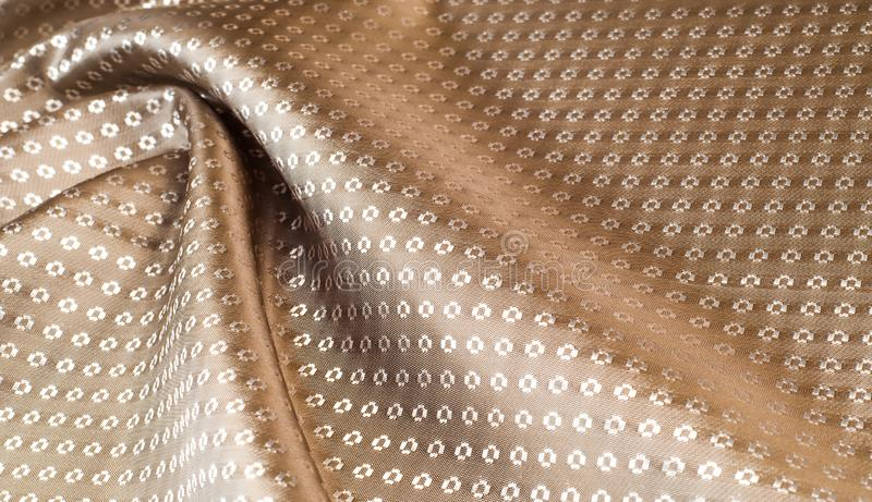 The texture of the silk fabric of beige with small white pattern. The texture of the silk fabric of  beige with small white pattern stock image
