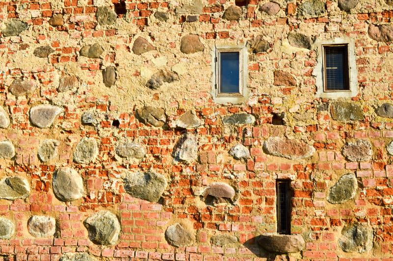 Texture with small narrow windows on an old ancient stone cracked dilapidated brick wall of red brick boulders. The background. Texture with small narrow windows stock photography