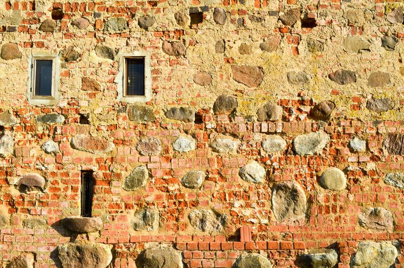 Texture with small narrow windows on an old ancient stone cracked dilapidated brick wall of red brick boulders. The background royalty free stock images