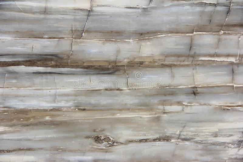 Texture of a smooth surface of a brown gray marble or tile wall with cracks, patterns and divorces. Texture of a smooth surface of brown gray marble or tile wall stock images