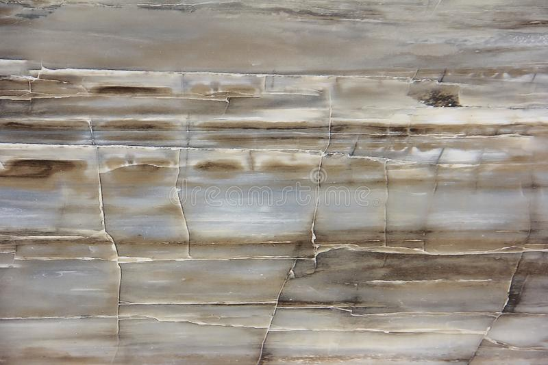 Texture of a smooth surface of a brown gray marble or tile wall with cracks, patterns and divorces. Texture of a smooth surface of brown gray marble or tile wall royalty free stock images