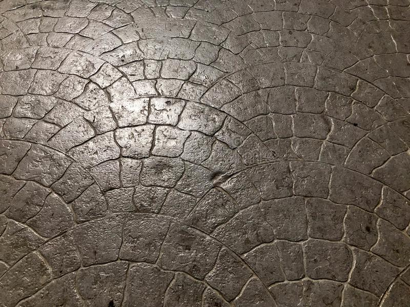 Texture of a stone concrete road tile shiny natural from bricks with a pattern of seams and cracks. The background.  royalty free stock images