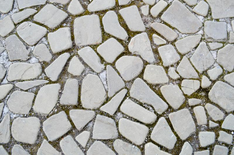 The texture of the stone road, pavement, walls of large gray old medieval round strong stones, cobblestones. The background royalty free stock image
