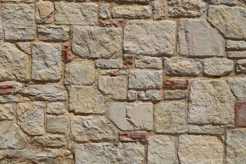 Texture of a stone wall.  House stone wall with square tiles texture background. Part of a stone fence, for background or texture royalty free stock images