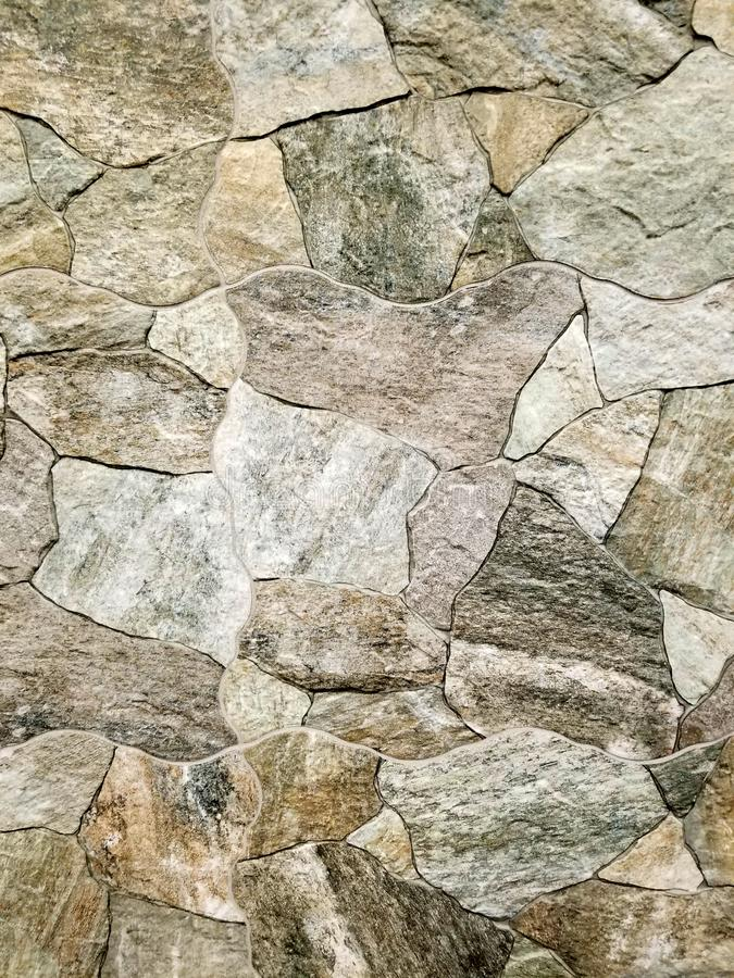 Texture - Stone wall made with man-made stone tiles in multiple colors. Providing a rustic look for indoor or outdoor environments royalty free stock image