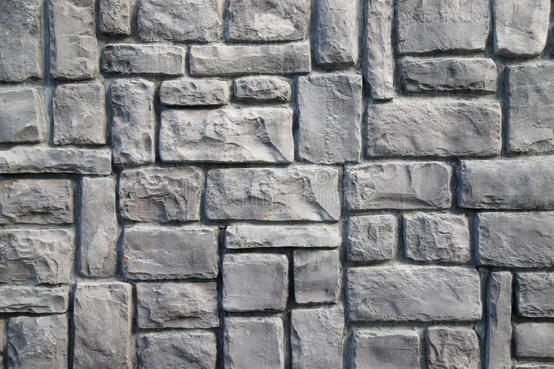 Texture of a stone wall made of rectangular blocks of different sizes painted in gray. As a background royalty free stock photo