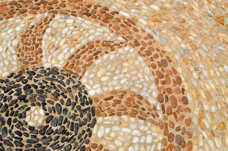The texture of the stone wall, the road from small round and oval stones with abstracted lines of heart patterns sandy. Seams of natural old yellow black brown stock image