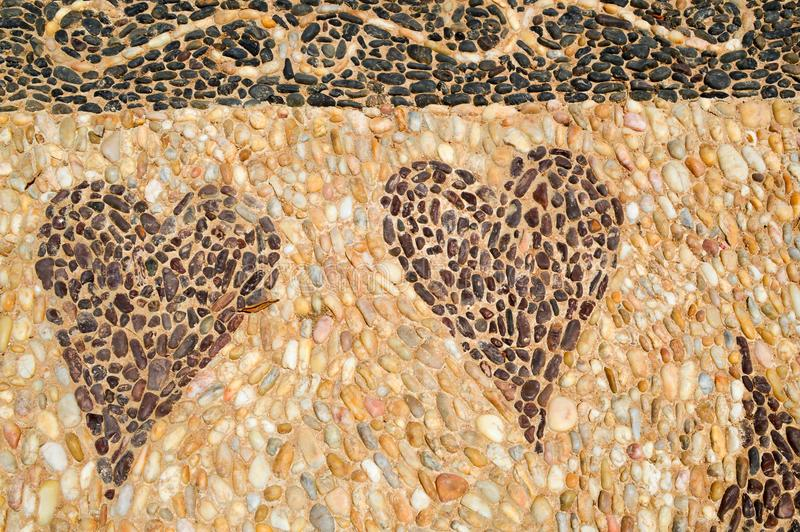 The texture of the stone wall, the road from small round and oval stones with abstracted lines of patterns of two hearts sandy royalty free stock images
