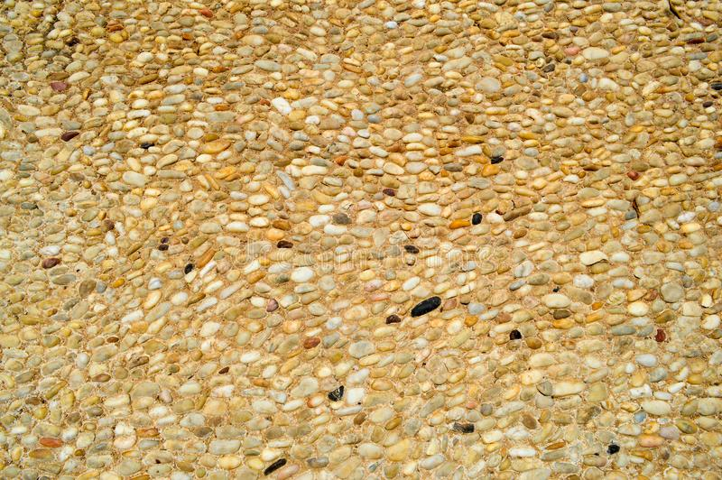 Texture of a stone wall, roads from small round and oval stones with sand with seams of natural old yellow black brown. background stock images