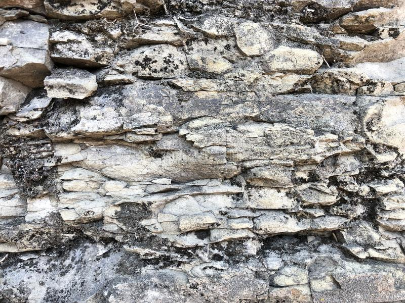 The texture of the stone wall of sharp cracked convex rough natural gray puff of old ancient stone bricks in the rock. stock image