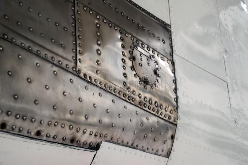 Texture surface of an old aircraft. Painted aluminum and stainless steel with rivets. Selective focus stock photo
