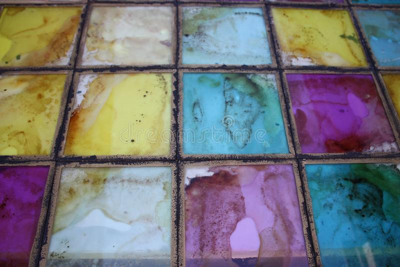 The texture of the colored glass stained glass tile. Texture texture glass mosaic stained glass sea blue purple yellow fading vintage rainbow tile royalty free stock photos