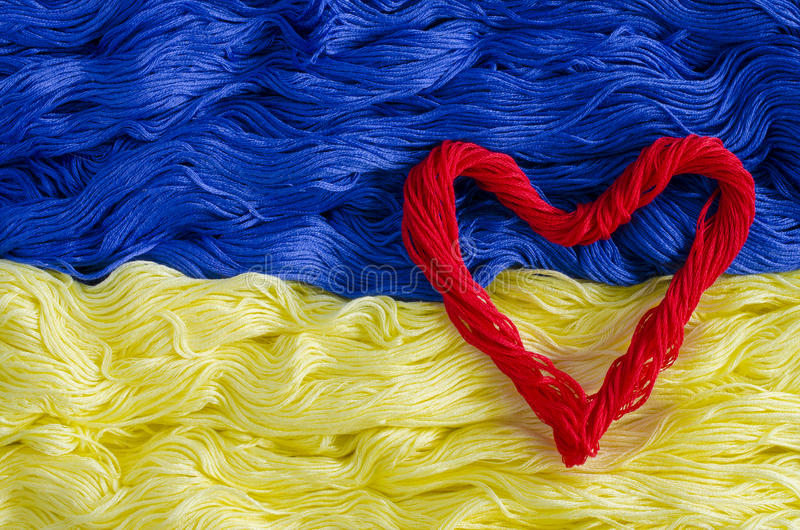 Texture thread with the image of the flag of Ukraine and heart. The texture of blue and yellow thread with a picture of the flag of Ukraine and the red thread in royalty free stock photos