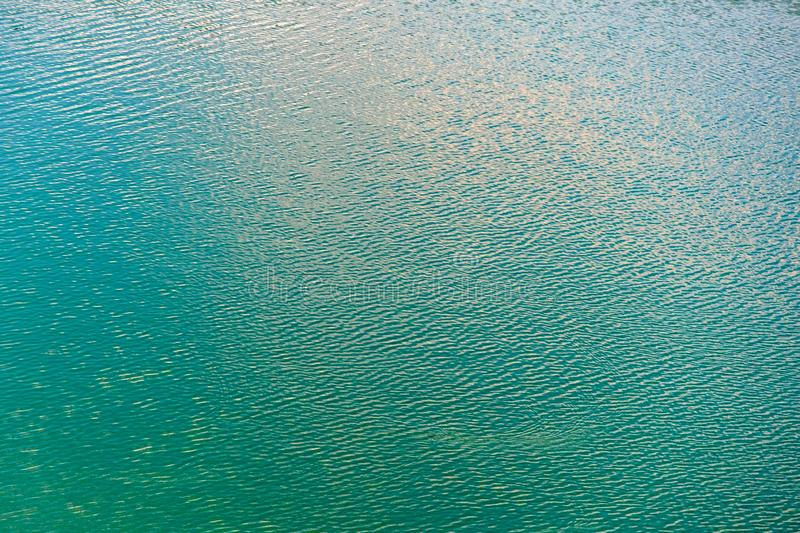 Texture of transparent clear surface of turquoise azure water with small ripples and sun reflections textured with waves royalty free stock images