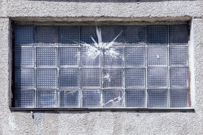 Cracked window after throwing stones and paint. stock photo