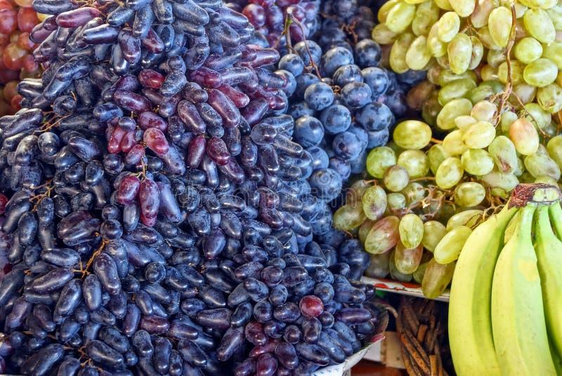 Texture végétative naturelle des baies mûres des raisins et des bananes de couleur bleue et jaune image libre de droits
