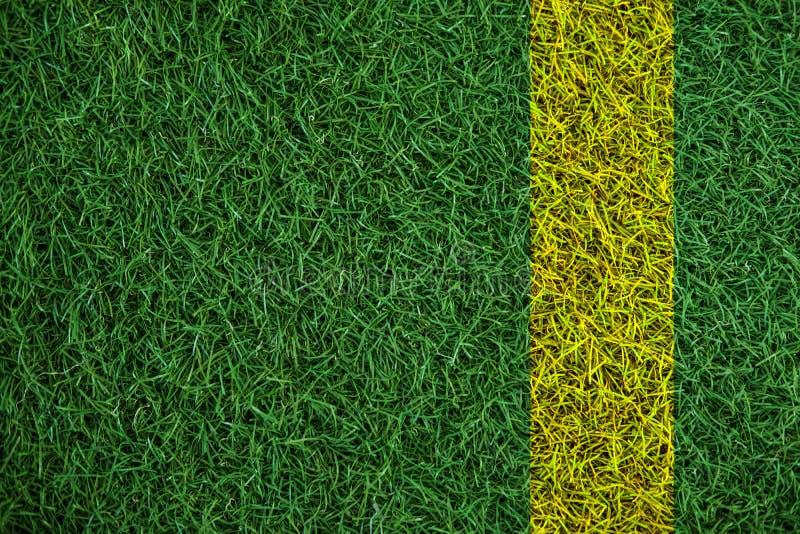 Texture verte d'herbe de gazon avec la ligne jaune, dans le terrain de football photographie stock