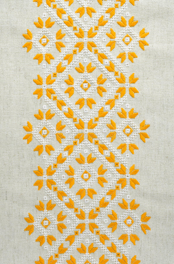 Texture of the vintage homespun linen textile with embroidery. Design of ethnic pattern. Craft embroidery. royalty free stock images