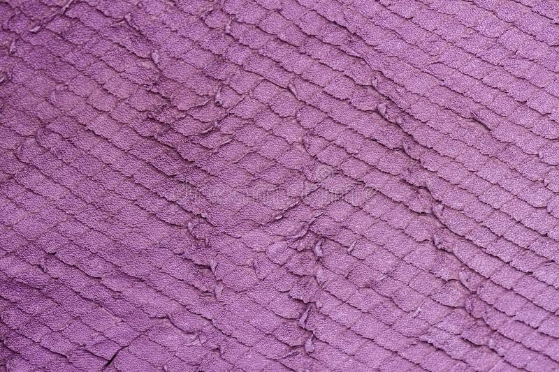Texture of violet purple genuine leather close-up, with embossed scales reptiles, fashion trend background royalty free stock photography