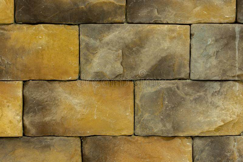 Texture, wall made of yellow brown decorative stone, building material large brick for decorating the outer wall, textured royalty free stock photography
