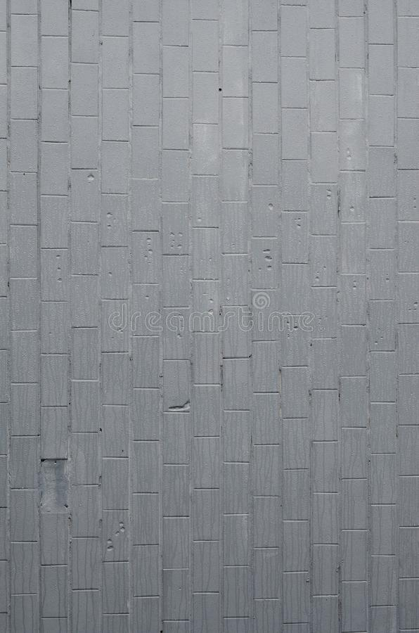 The texture of the wall from the old tile, painted gray under the influence of condensation. A lot of small drops and water stains. On the wall royalty free stock photo