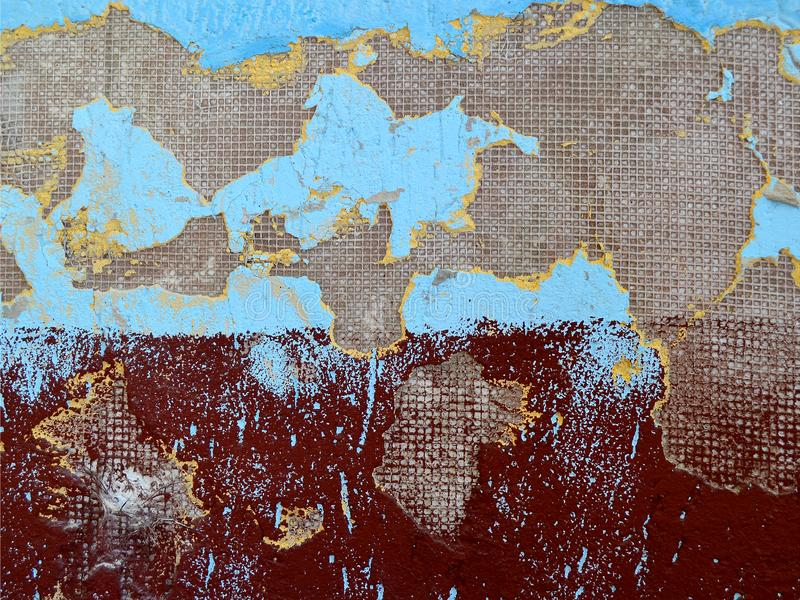 Texture of the wall, painted in blue and burgundy colors with damaged plaster looks like a map of the world stock photography