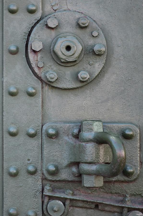 The texture of the wall of the tank, made of metal and reinforced with a multitude of bolts and rivets. Images of the covering of stock photography