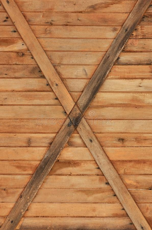 The texture of weathered wooden wall. Texture of an old fence of horizontal orange wooden planks with cross-board. S royalty free stock photo